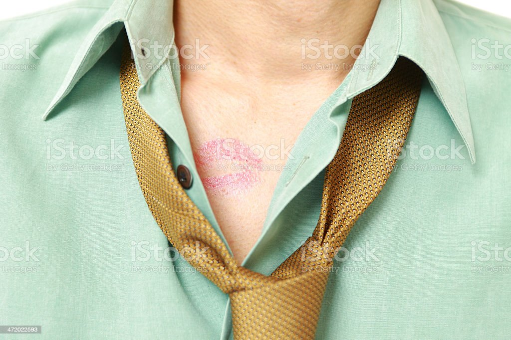 Man wearing green shirt and gold tie with pink lip marks stock photo