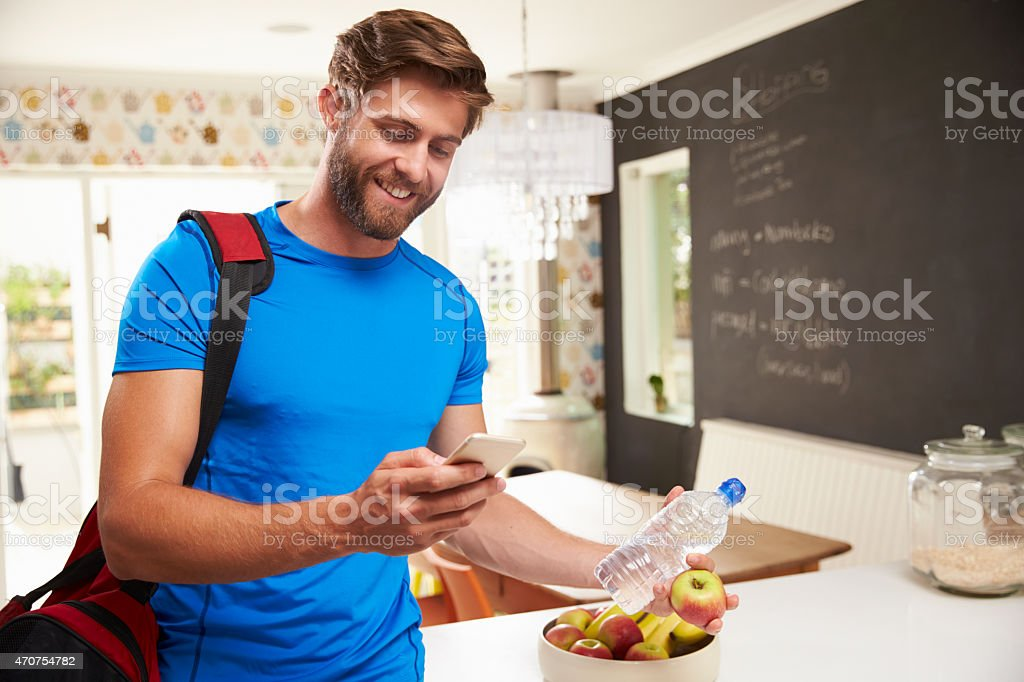 Man wearing gym clothes smiling and looking at a cell phone stock photo