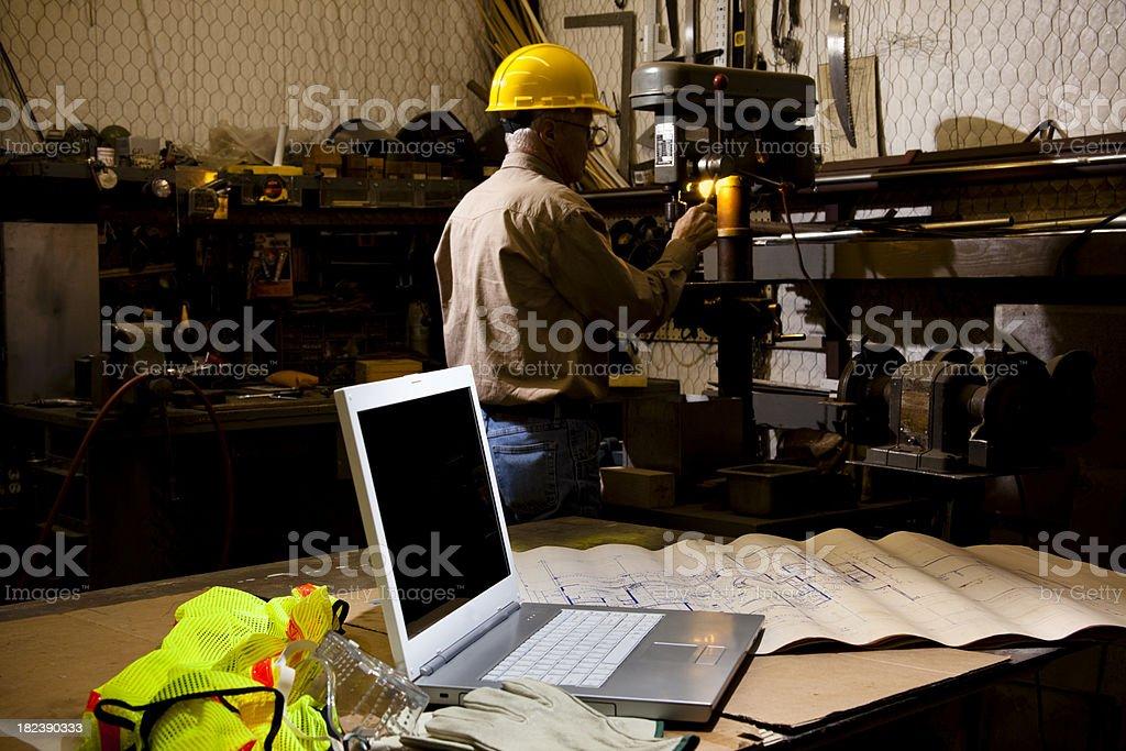Man wearing hardhat working in workshop.  Laptop on workbench royalty-free stock photo