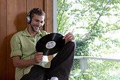 Man wearing headphones, holding long playing record