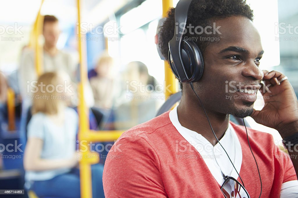 Man Wearing Headphones Listening To Music On Bus Journey stock photo