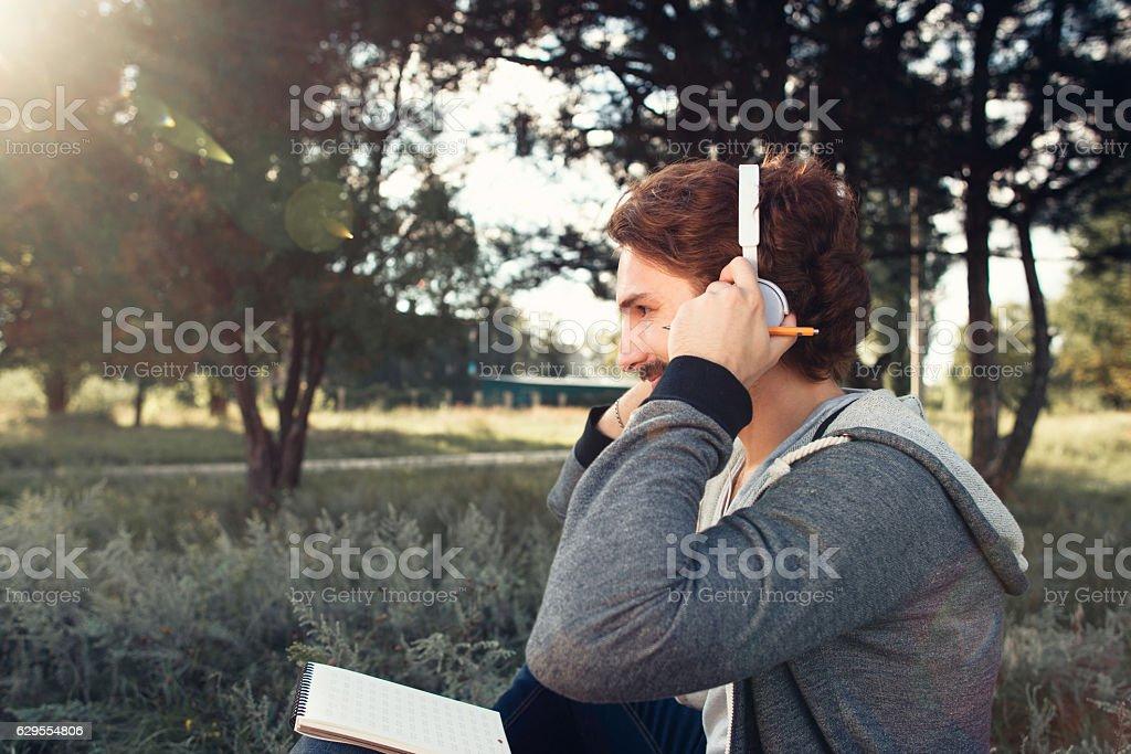 Man wearing headphones, relaxing at nature stock photo