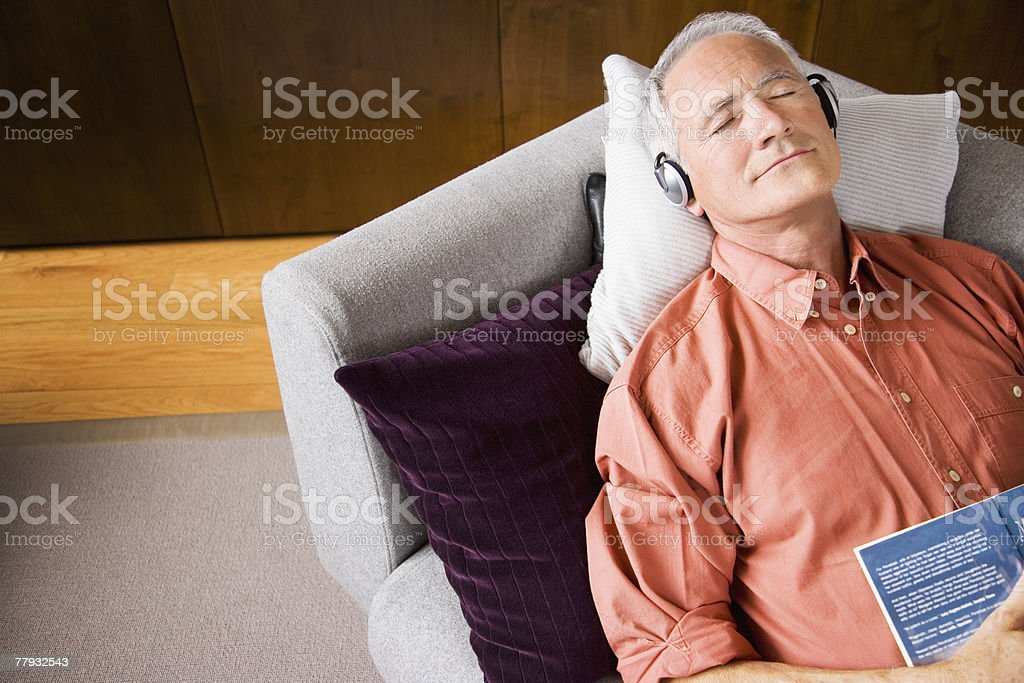 Man wearing headphones sleeping on sofa with book royalty-free stock photo
