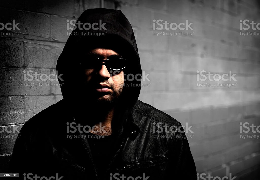 Man wearing hood and glasses standing in front of wall royalty-free stock photo