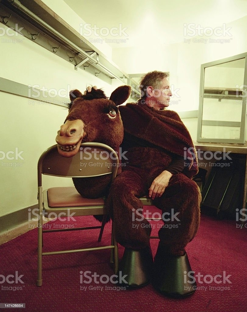 Man wearing horse costume, sitting in dressing room stock photo