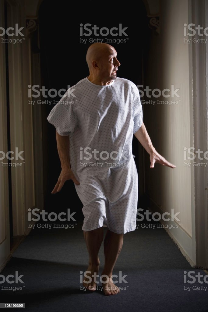Man Wearing Hospital Gown and Running Down Hallway stock photo
