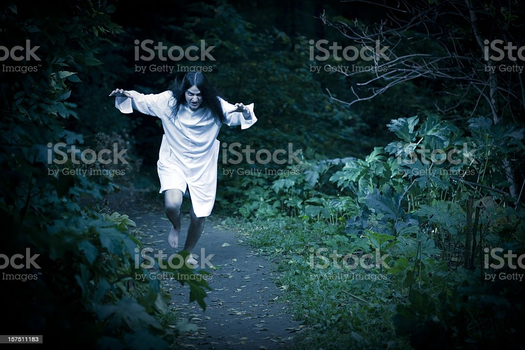 Man Wearing Hospital Gown and Running through the forest royalty-free stock photo