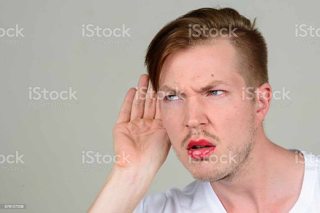 Man wearing make up cupping his ear with his hand stock photo