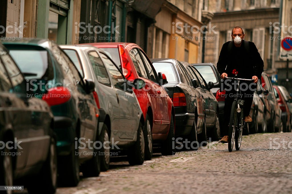 Man wearing mask biking down car lined cobblestone road royalty-free stock photo