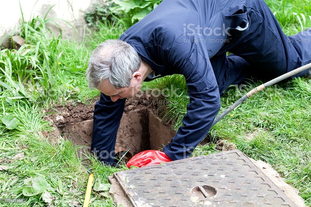 Man wearing overalls leaning into outdoor drain stock photo
