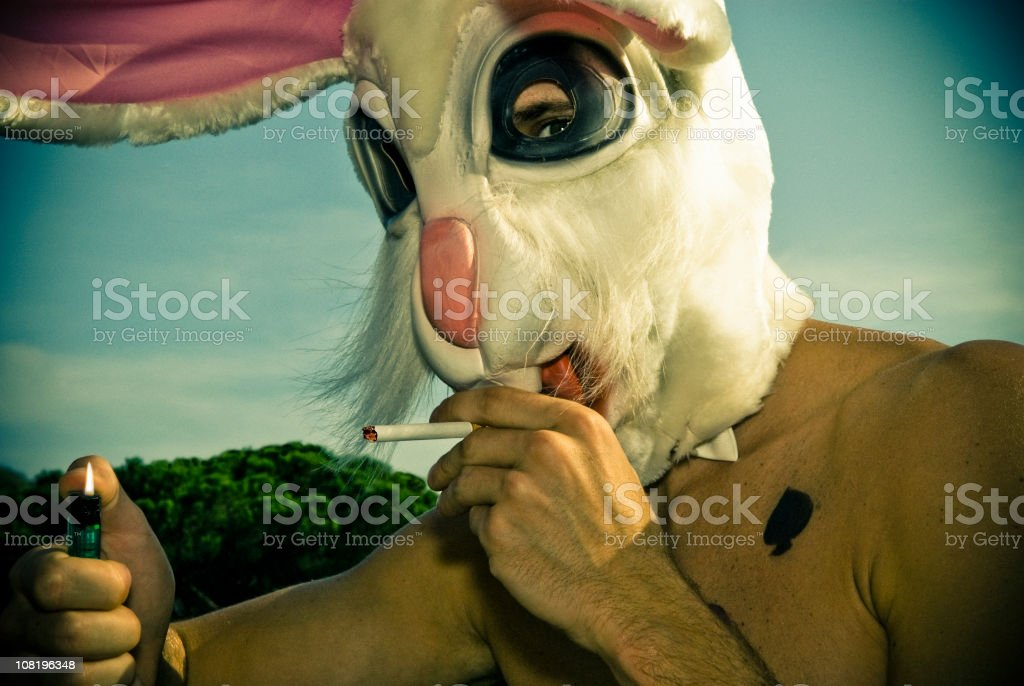 Man Wearing Rabbit Mask Lighting Cigarette stock photo