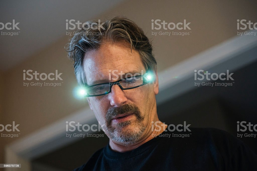 Man wearing reading glasses with lights stock photo