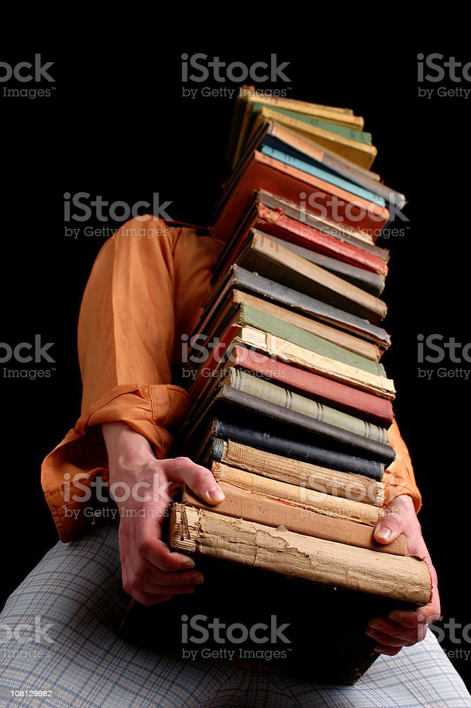 Man Wearing Retro Clothing Carrying Large Stack of Old Books royalty-free stock photo