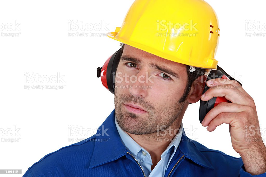 Man wearing safety earmuffs and helmet stock photo