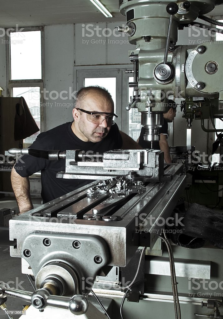 Man wearing safety glass working with large machine stock photo