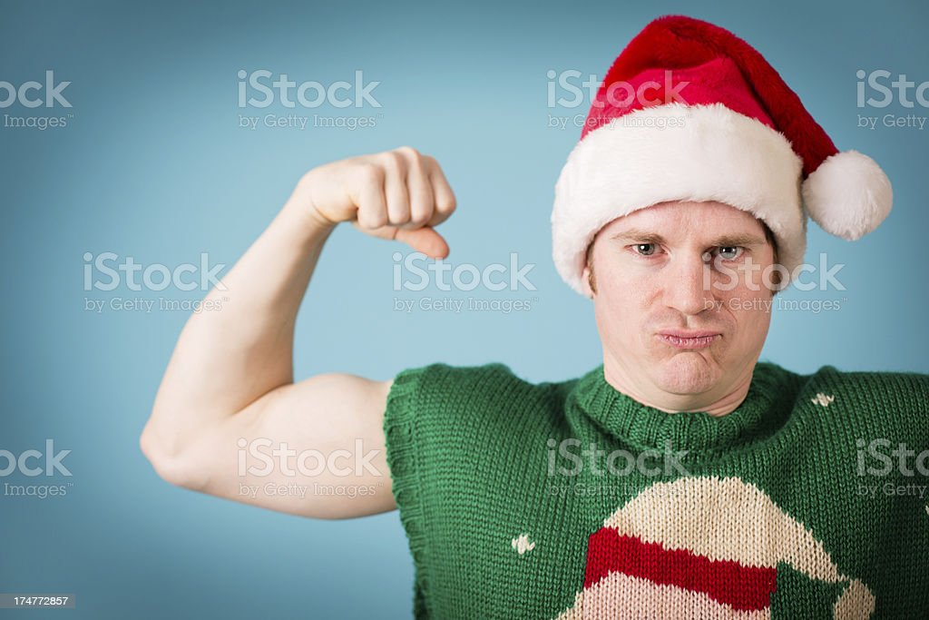 Man, Wearing Santa Hat and Christmas Vest, Flexing His Muscles royalty-free stock photo