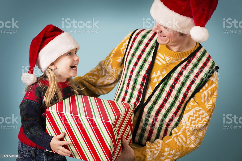 Man Wearing Santa Hat Giving Present to Little Girl royalty-free stock photo