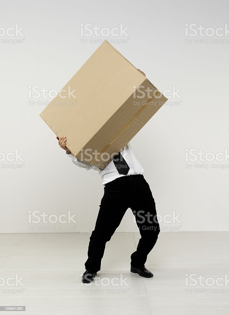 Man wearing shirt and tie carrying a large cardboard box stock photo