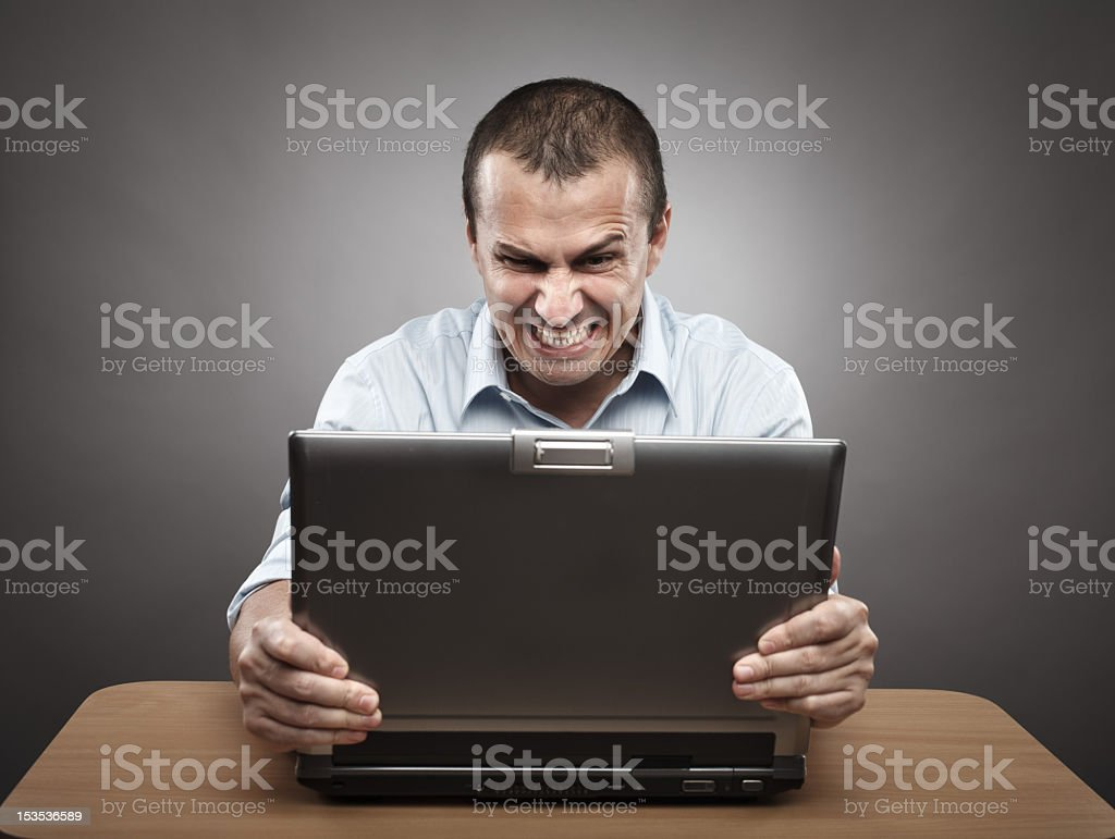 Man wearing shirt looking angry whilst grasping laptop royalty-free stock photo