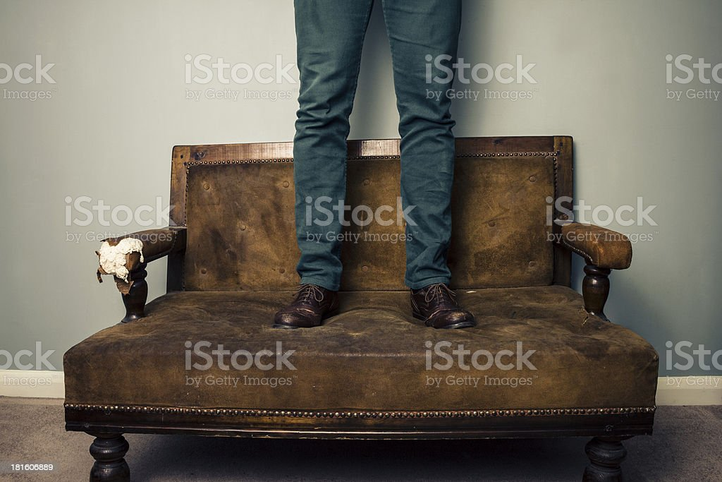 Man wearing shoes standing on sofa royalty-free stock photo