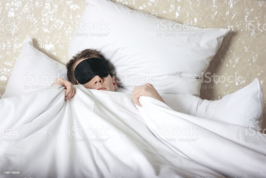 Man Wearing Sleeping Mask in Bed stock photo