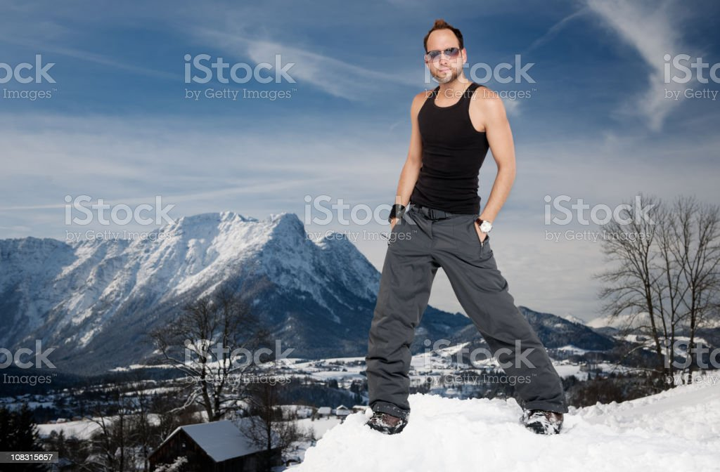 Man wearing snow pants and vest in front of  Alps royalty-free stock photo