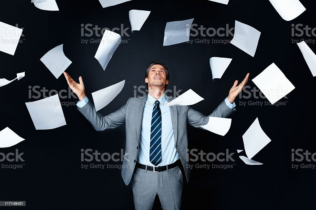 Man wearing suit looking up at papers in the air royalty-free stock photo