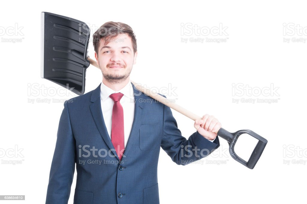 Man wearing suit smiling and carrying a snow shovel stock photo