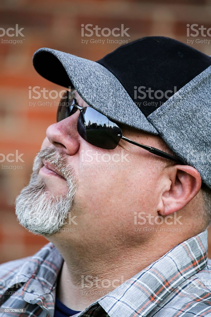 Man Wearing Sunglasses and Hat Looks Up stock photo