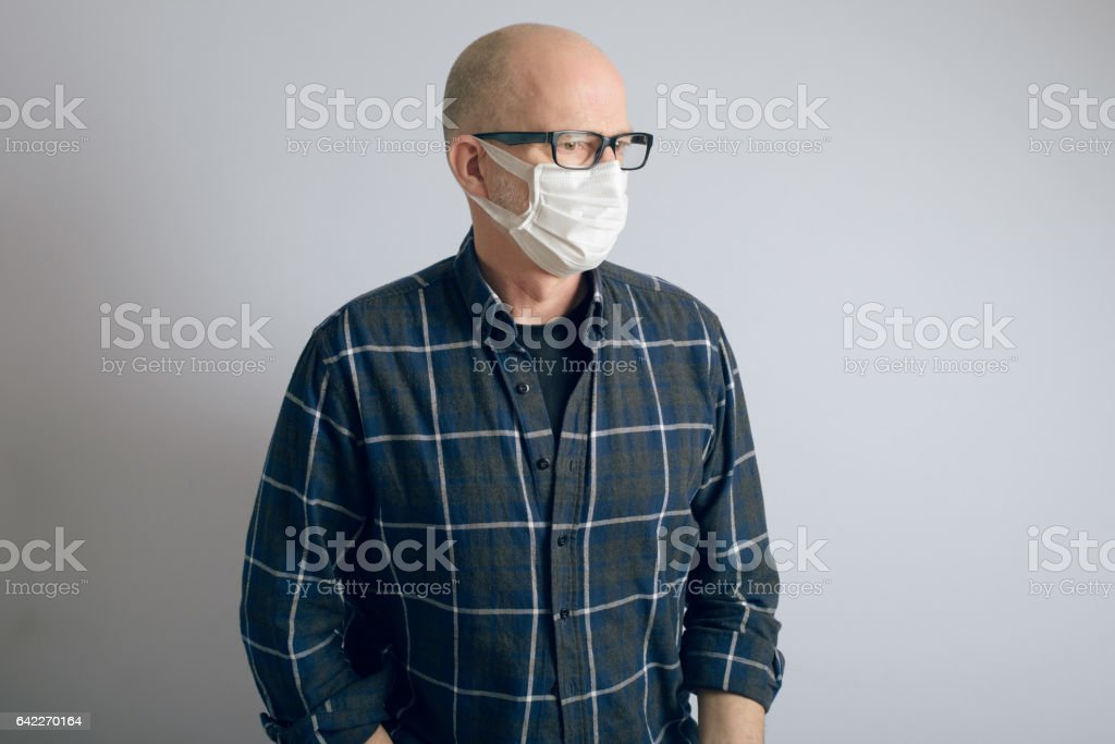 Man Wearing Surgical Style Face Mask Against Air Pollution stock photo
