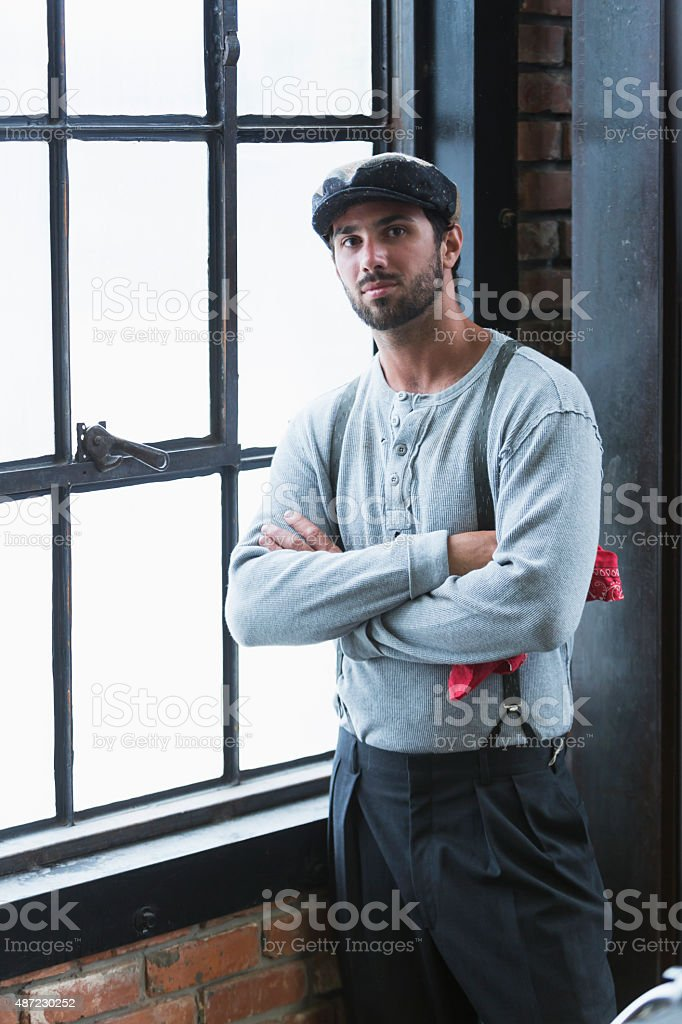 Man wearing suspenders standing by window stock photo