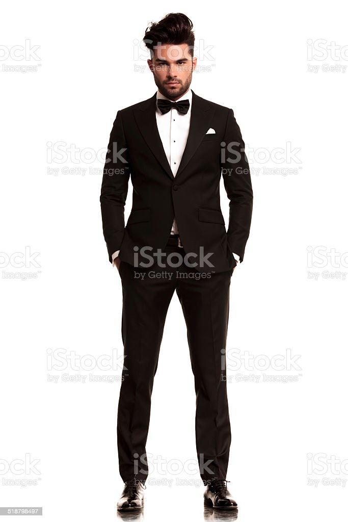 man wearing tuxedo standing with hands in pockets stock photo