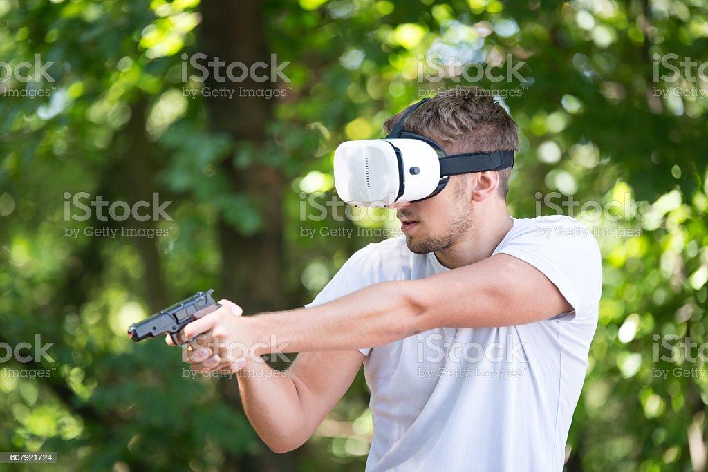 Man wearing virtual reality goggles, gun stock photo