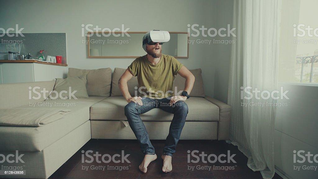 Man wearing virtual reality headset at home stock photo