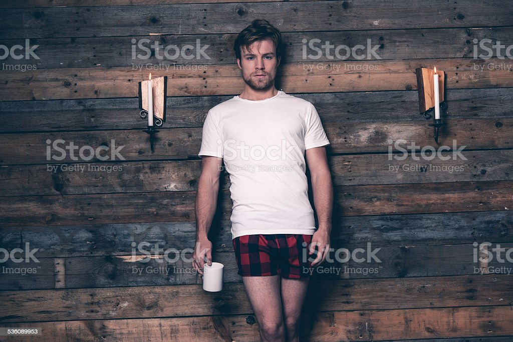 Man wearing white t-shirt and red flannel shorts. stock photo