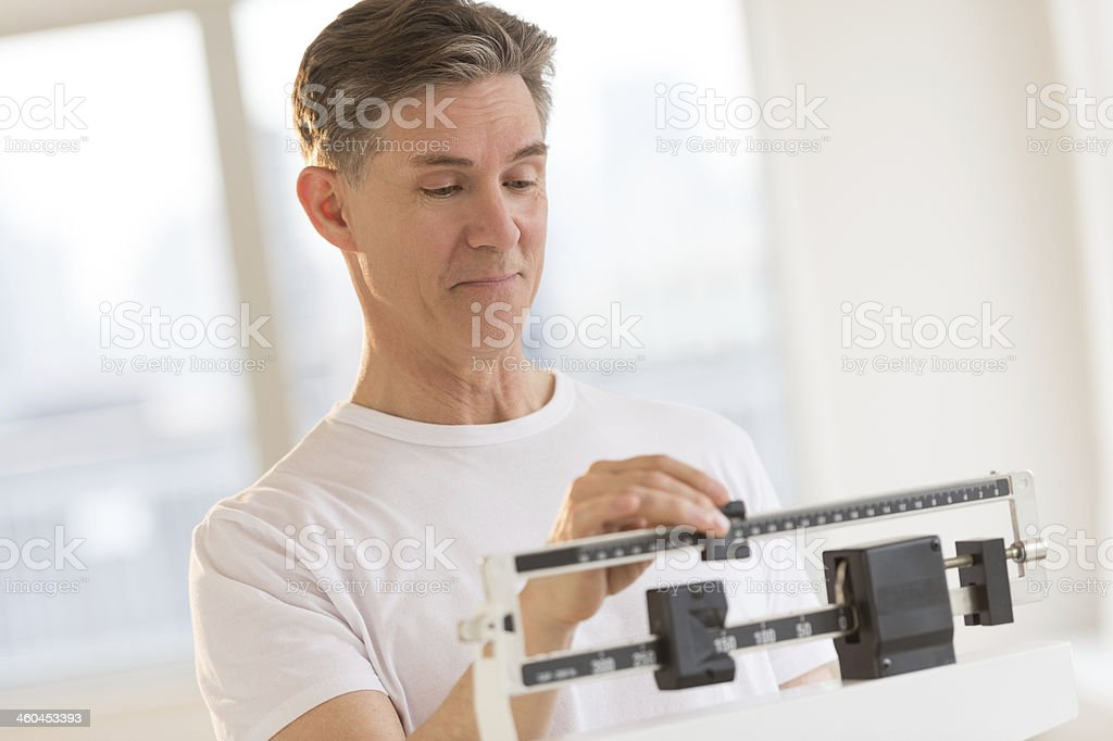 Man Weighing Himself On Balance Weight Scale stock photo