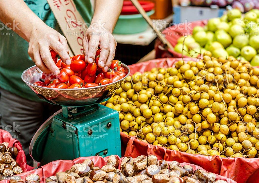 man weighing tomatoes at street market in Hong Kong, China stock photo
