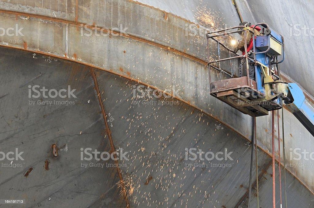 Man welding seams on hull of ship under construction stock photo