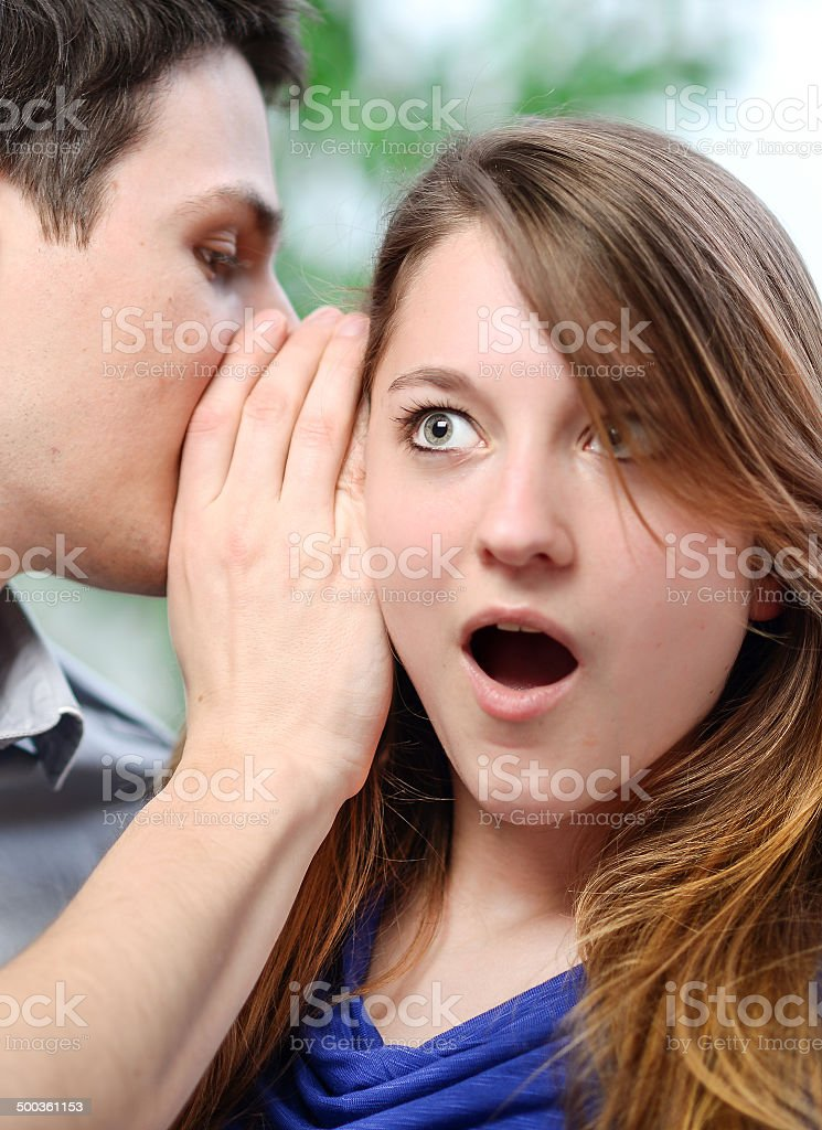 man whispering in the ear of his surprised wife royalty-free stock photo