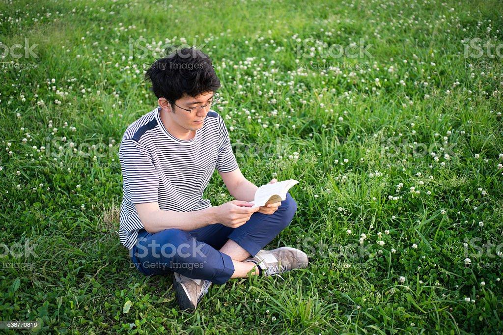 Homme qui indique un livre sur une pelouse photo libre de droits