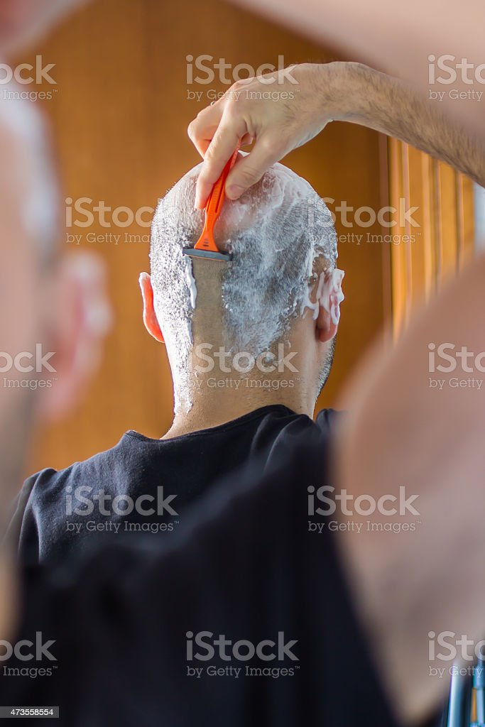 man who shaves his head stock photo