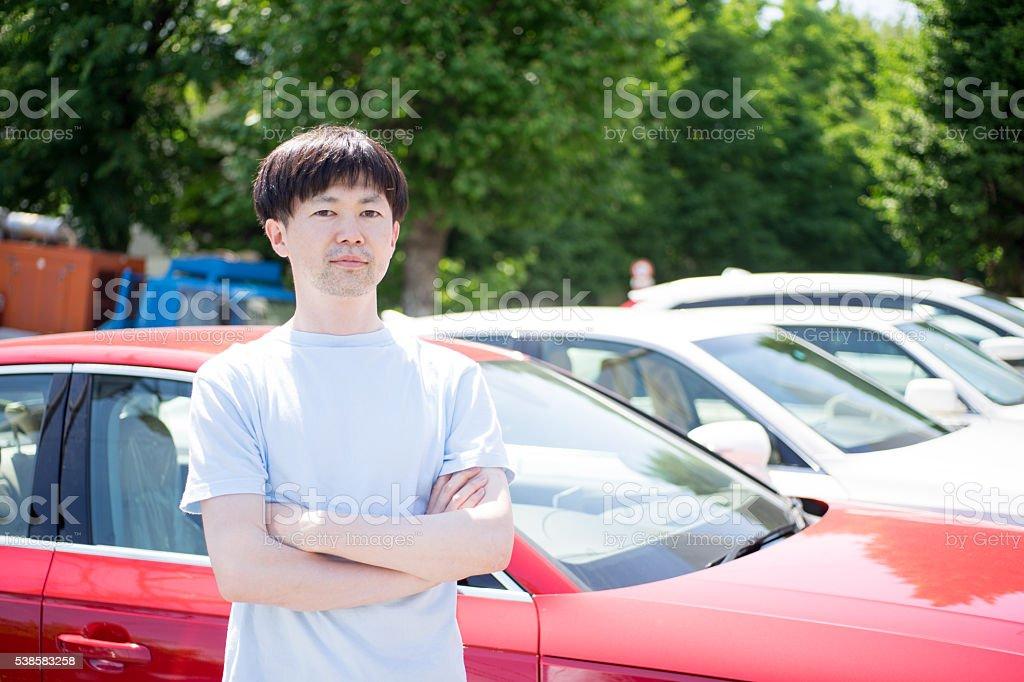 Homme qui se trouve avant une voiture photo libre de droits