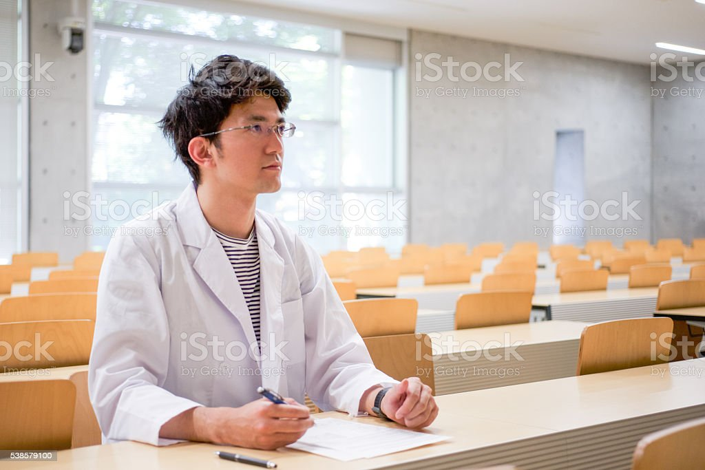 Man who takes a lecture with a white robe figure stock photo