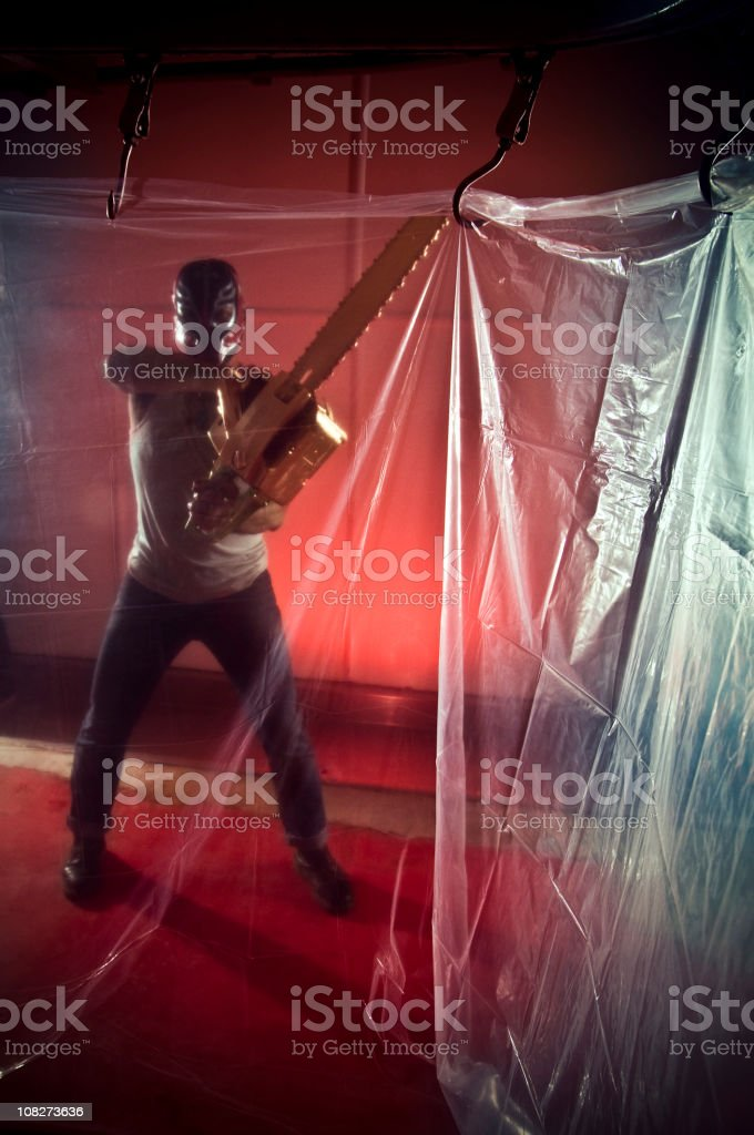 Man Wielding Chain Saw in Plastic Covered Room stock photo