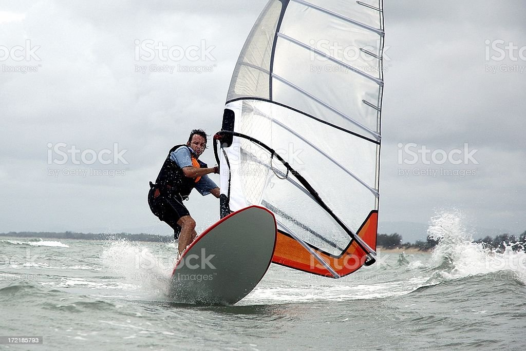 Man Windsurfing in the waves on a cloudy day stock photo