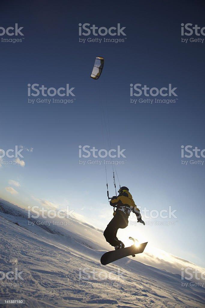 Man windsurfing on snowboard stock photo