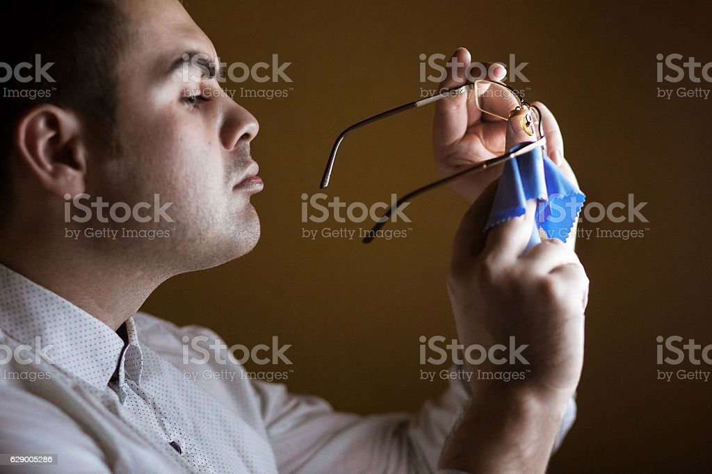 Man wipes with a softie of  lens  computer glasses stock photo