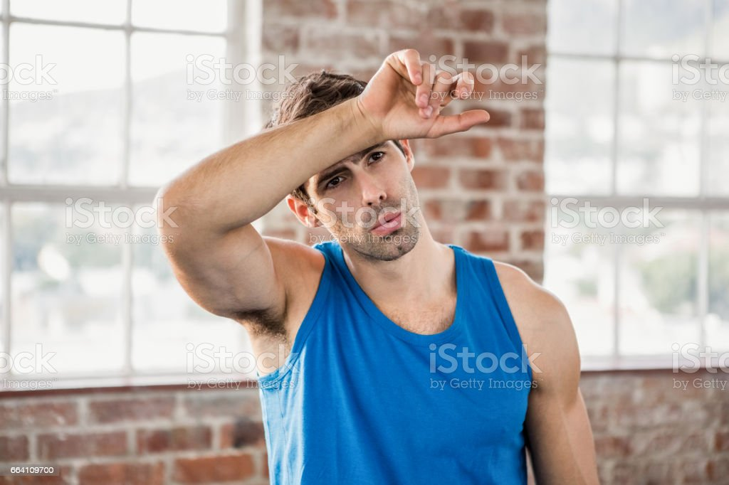 Man wiping his forehead with arm stock photo
