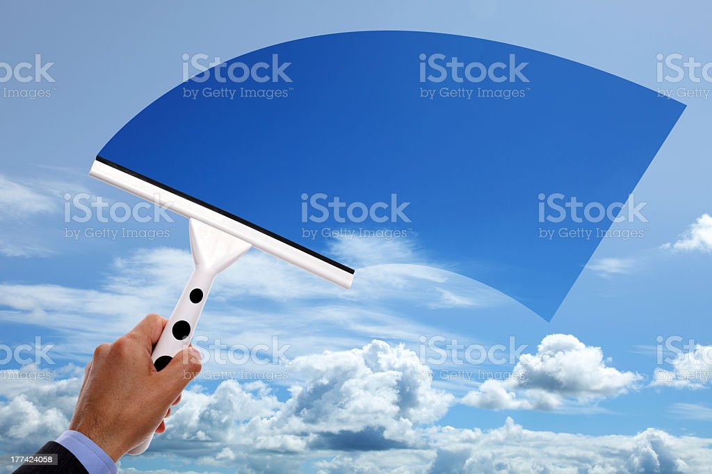 Man wiping the sky with squeegee to make it bluer stock photo