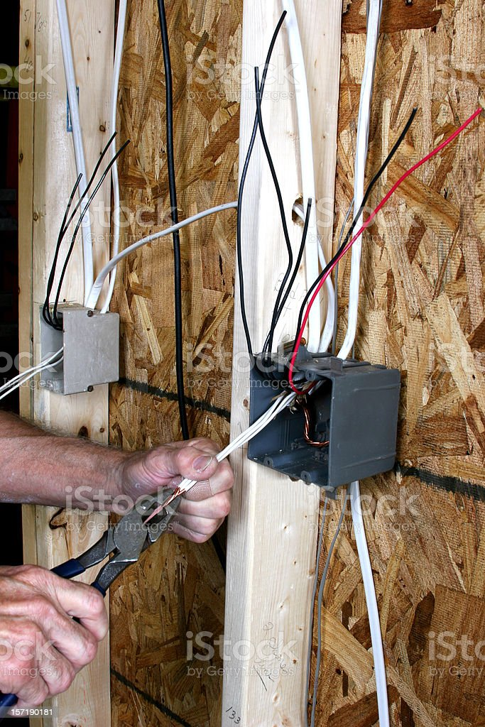 Man wiring an electrical switch box. New construction home. stock photo